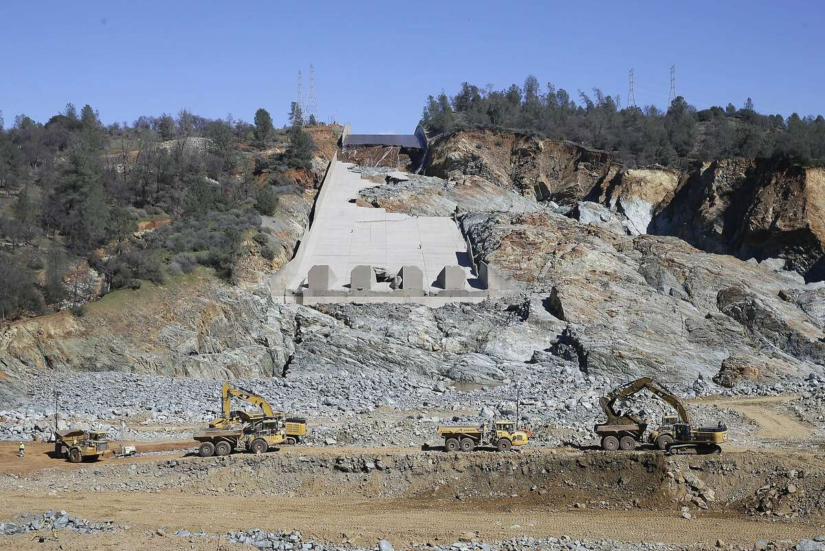FILE - In this Feb. 28, 2017, file photo, construction crews clear rocks away from Oroville Dam's crippled spillway in Oroville, Calif. With stormy weather approaching, California plans to resume releasing water down the damaged spillway at the nation's tallest dam. (AP Photo/Rich Pedroncelli, File)