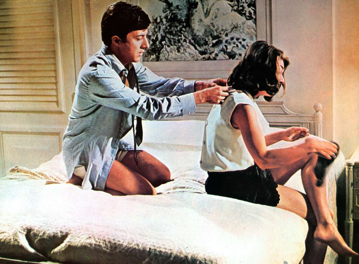 Dustin Hoffman on bed with Anne Bancroft in a scene from the film 'The Graduate', 1967.