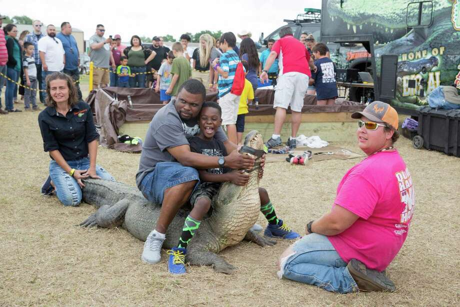 Flanked by Melizza Atkinson and Daniel Cook, John Pate and his son Jabon, 7, sit on an 11-foot alligator after a Gator Country show at the Poteet Strawberry Festival in Poteet, Texas on April 9, 2017. Ray Whitehouse / for the San Antonio Express-News Photo: Ray Whitehouse, Photographer / For The San Antonio Express-News
