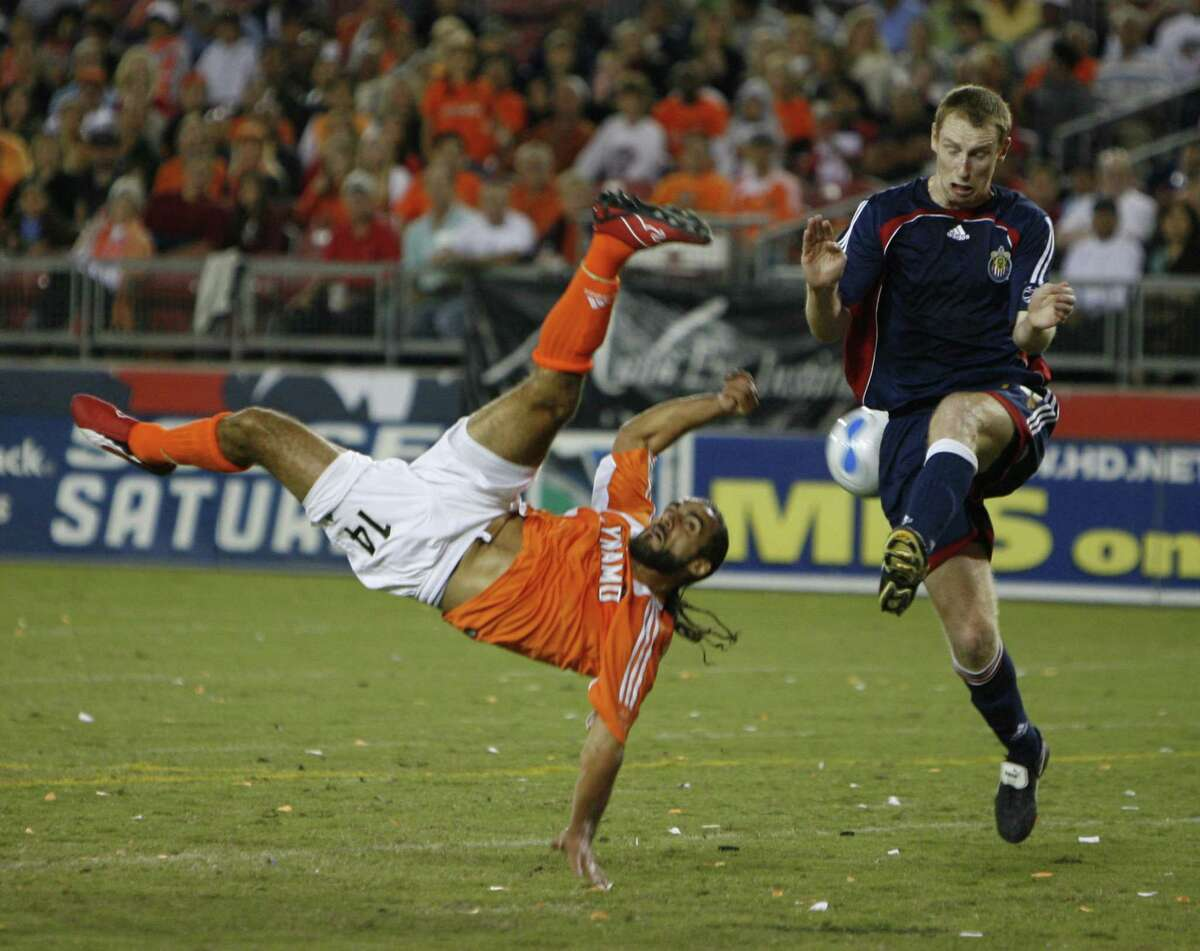 Dynamo's #14, Dwayne De Rosario flips as he takes a shot on goal against Chivas' #24, Tim Regan during the first half of the Dynamo-Chivas soccer playoff soccer game, Sunday, October 29, 2006. (Karen Warren/ Houston Chronicle)