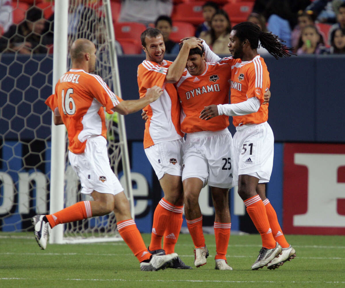 Houston Dynamo forward Brian Ching (25) is congratulated by teammates Craig Waibel (16), Eddie Robinson, and Adrian Serioux (51) after Ching scored a goal past Colorado Rapids goalkeeper Joe Cannon in the first half of a soccer game in Denver, Saturday, April 29, 2006. (AP Photo/Jack Dempsey)