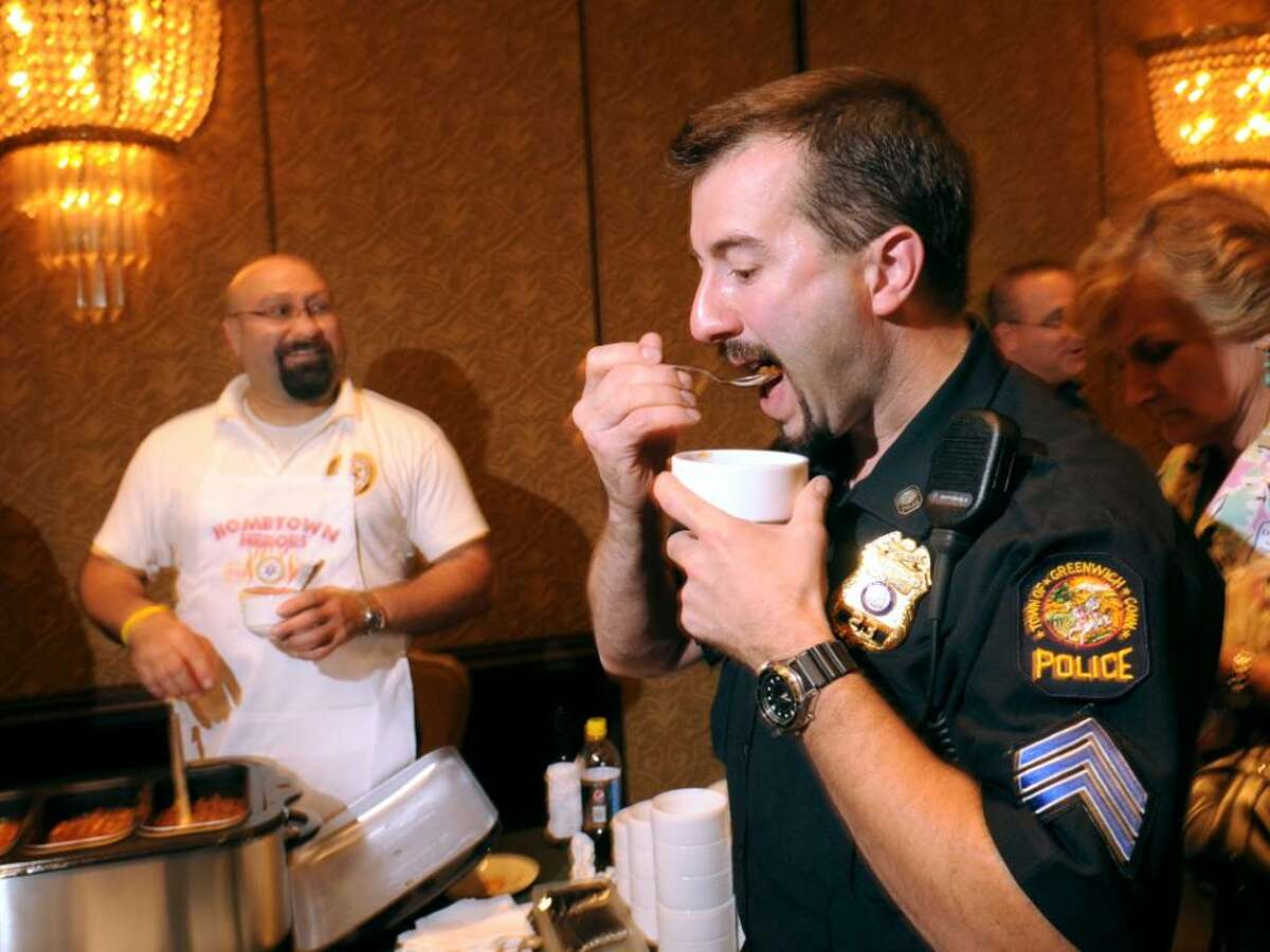 Greenwich police Sgt., Brent Reeves, right, samples the chili of John Castagna of the Greenwich Emergency Medical Service, left, during the chili challenge which pitted the Greenwich police, GEMS and two Glenville firefighters in a chili cook-off competition. Reeves said he thought Castagna's chili was good saying it had a sweet taste but he ultimately favored the chili of fellow police officer, Jeff Loock (cq), because of the meats in Loock's chili was venison, during the Greenwich Chamber of Commerce Business and Culinary Showcase at the Greenwich Hyatt, Thursday evening, June 3, 2010.