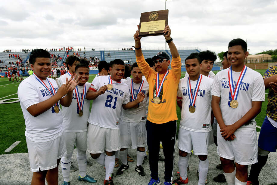 Washington Head Boys Soccer Coach Francisco Porras, center, hoists the team plaque after the Golden Eagle's 4-0 loss to the Kilgore Bulldogs in their Class 4A Boys semifinal matchup at the state soccer tournament at Birkelbach Field in Georgetown on Wednesday. (Photo by Jerry Baker/Freelance) Photo: Jerry Baker/For The Chronicle