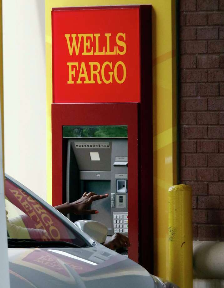 In this April 11, 2017, photo, a customer uses a drive-thru ATM at a Wells Fargo bank in northeast Jackson, Miss. On Thursday, April 13, 2017, Wells Fargo reported earnings. Wells Fargo's first-quarter profit was essentially flat from a year earlier as new customers continue to stay away from the bank following its sales practice scandal. (AP Photo/Rogelio V. Solis) Photo: Rogelio V. Solis, STF / Copyright 2017 The Associated Press. All rights reserved.