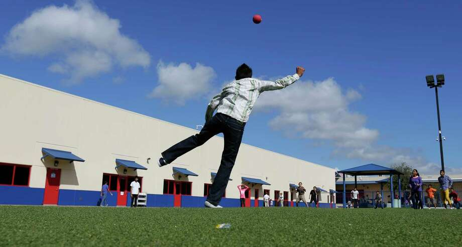 FILE - In this Sept. 10, 2014, file photo, detained immigrant children play kickball at the Karnes County Residential Center, a temporary home for immigrant women and children detained at the border in Karnes City, Texas. The GEO Group, a private prison company, announced Thursday, April 13, 2017, it has won a $110-million federal contract to build in Texas the first new immigrant detention center under the Trump administration. The company said that the 1,000-bed detention facility will be in Conroe, Texas, north of Houston. It's scheduled to open by December 2018. (AP Photo/Eric Gay, File) Photo: Eric Gay, STF / Copyright 2017 The Associated Press. All rights reserved.