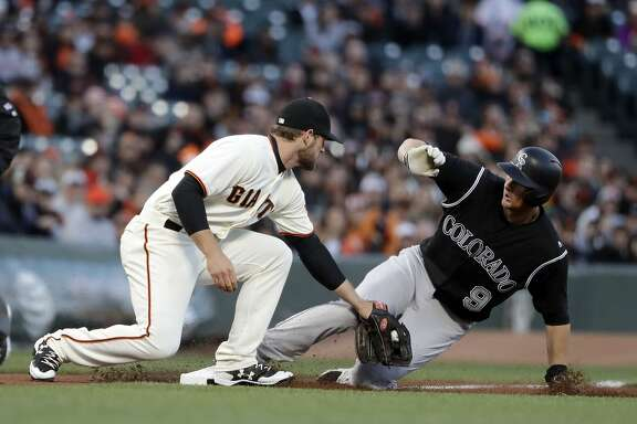 Colorado Rockies' D.J. LeMahieu (9) steals third base past the tag from San Francisco Giants third baseman Conor Gillaspie during the first inning of a baseball game, Thursday, April 13, 2017, in San Francisco . (AP Photo/Marcio Jose Sanchez)