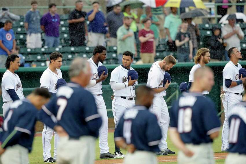 San Antonio players endure a steady rain during the national anthem as the Missions host Northwest Arkansas at Wolff Stadium on April 13, 2017.