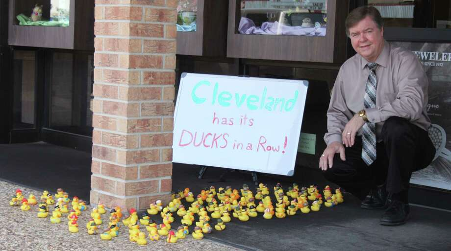 Coats Jewelers Owner Bobby Coats kneels next to 150 rubber ducks placed outside of his store in the early morning hours Thursday, April 13. No one has claimed responsibility for placing this second group of rubber ducks. The first was discovered last week outside of the Hometown Sears Store in Cleveland. Photo: Jacob McAdams