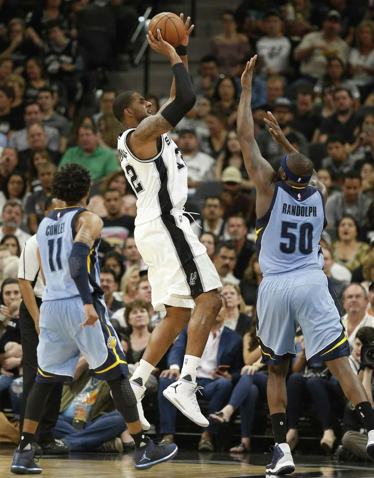 Spurs' LaMarcus Aldridge (12) attempts a shot against the Memphis Grizzlies' Zach Randolph (50) and Mike Conley (11) at the AT&T Center on April 4, 2017.