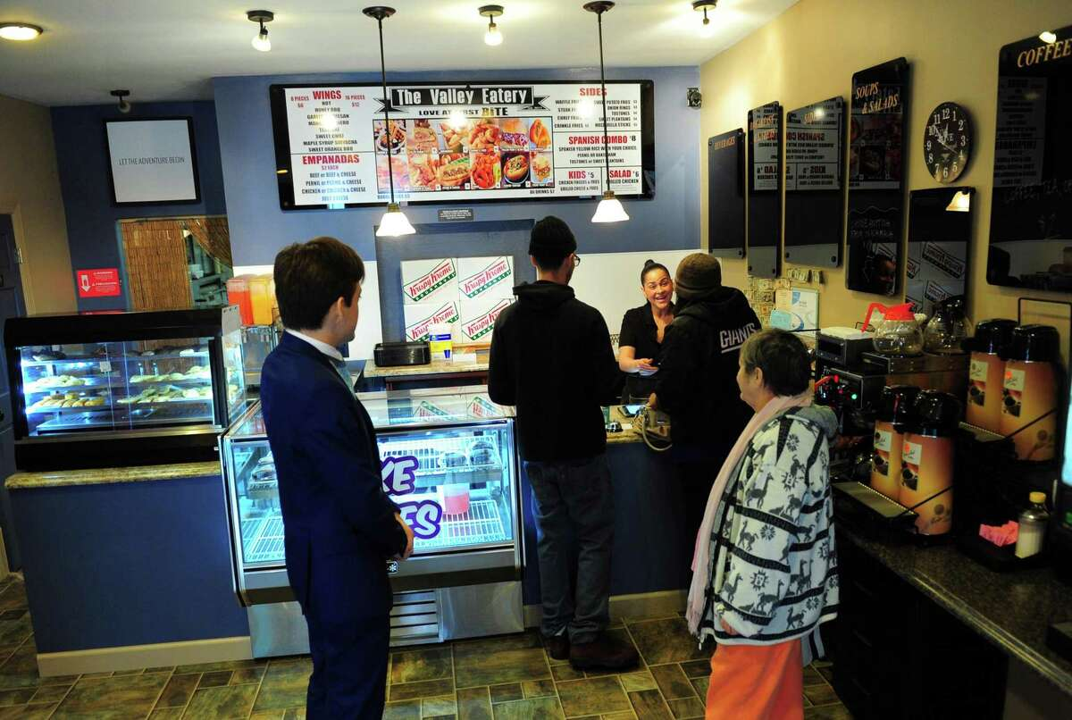 Natasha Aviles waits on customers at The Valley Eatery on Main Street in Ansonia, Conn. on Friday Apr. 7, 2017. The new downtown eatery features a Krispy Kreme burger (bacon atop a cheeseburger between two Krispy Kreme donuts) and a cake shake which is a piece of cake blended with ice cream and milk.