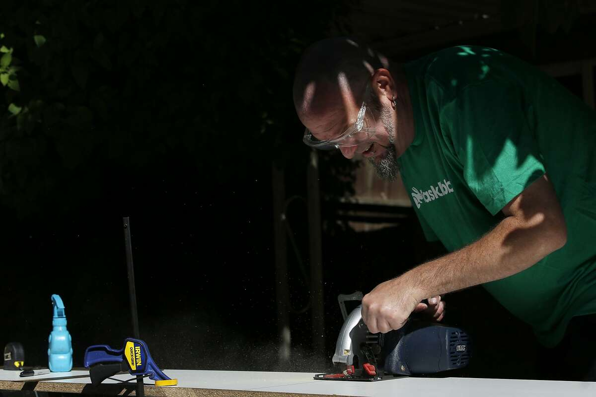 Duncan Cook cuts wood for a client's custom shelf on Thursday, April 13, 2017, in San Jose, Calif. Cook left his full-time job to become a task rabbit.