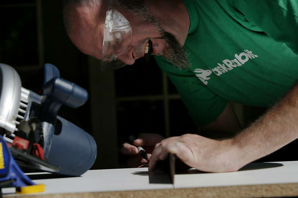 Duncan Cook marks wood to cut for a client's custom shelf on Thursday, April 13, 2017, in San Jose, Calif. Cook left his full-time job to become a task rabbit.