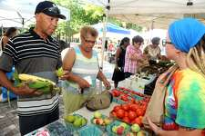 Calvin Washington, left, of Bridgeport buys corn and fruit from Amanda Hill, right, from Killam & Bassette Farmstead in South Glastonbury, at the weekly Farmer's Market held in McLevy Square, in Bridgeport, Conn. Aug. 11, 2016. The market is open every Thursday afternoon.
