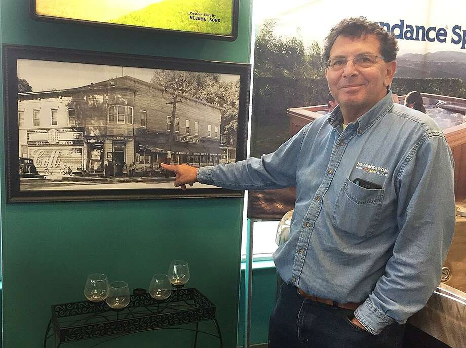 Tom Nejame of Nejame & Sons points on Tuesday, April 4, 2017, to an undated photograph of the general store that opened in 1921 and was the start of the Nejame family business in Danbury, Conn. Photo: Chris Bosak / Hearst Connecticut Media / The News-Times