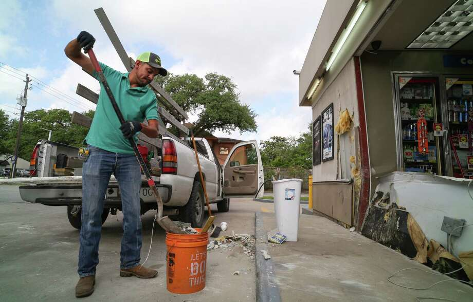 Ismael Sanchez cleans up debris left from a smash and grab ATM robbery at the Star Stop store on West Alabama and Montrose Blvd. Thursday, April 14, 2017, in Houston. Photo: Godofredo A. Vasquez / Houston Chronicle