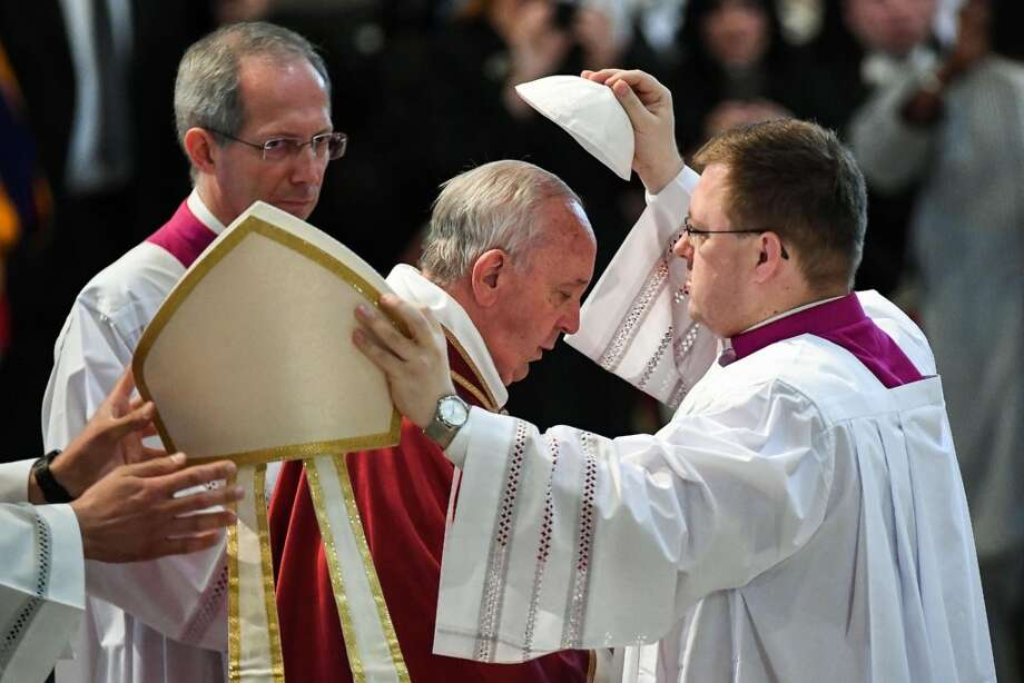 Pope Francis is helped to wear his skullcap during the Good Friday Passion of Christ service inside St. Peter's Basilica at the Vatican on Friday. Photo: Associated Press