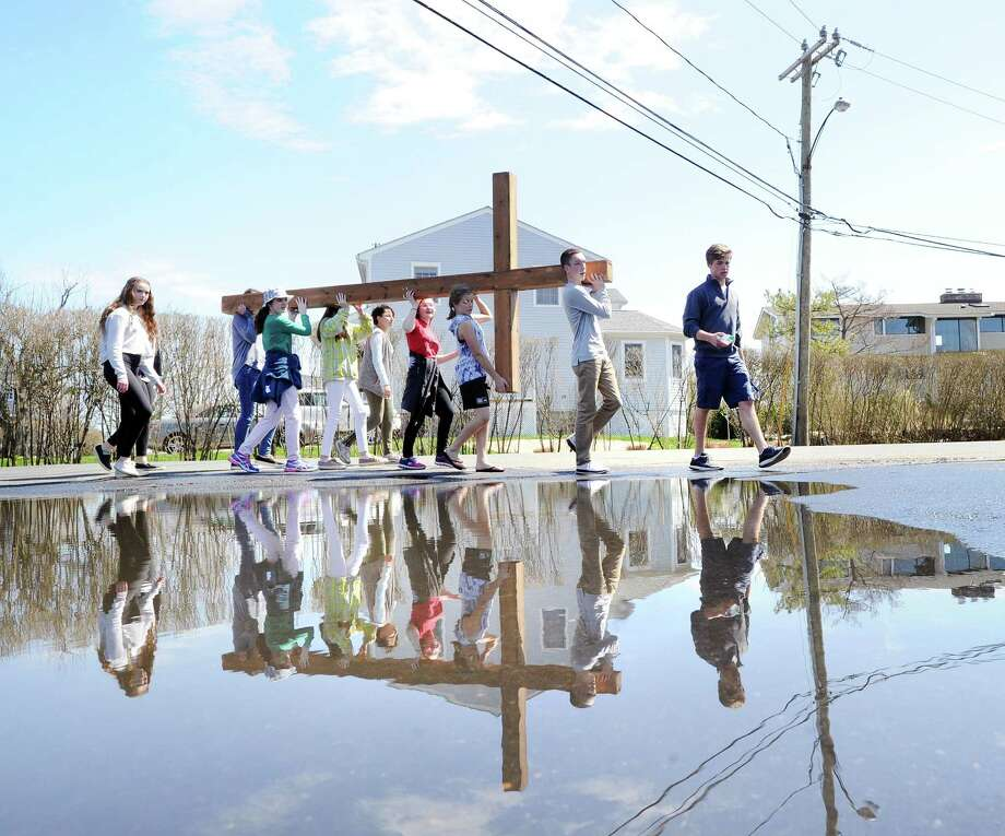 Drew Mohn, 17, right, leads the First Congregational Church of Greenwich Youth Group Cross Walk around a puddle on Shore Road in Old Greenwich, Conn., Good Friday, April 14, 2017.  Rev. Patrick Collins, First Congregational Church Associate Pastor of Children, Youth and Families, who was supervising the cross walk, said the group of about 10 kids carried the cross from Binney Park to Greenwich Point and that the cross will be used for the Easter Sunday sunrise service that takes places at 6 a.m. on the beach at Greenwich Point. Photo: Bob Luckey Jr. / Hearst Connecticut Media / Greenwich Time