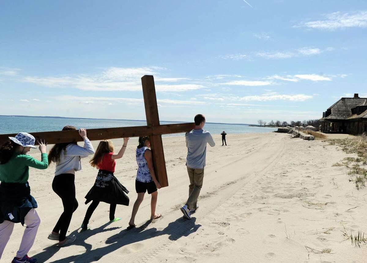 The First Congregational Church of Greenwich Youth Group Cross Walk, lead by Dan Lepoutre, 18, right, makes its way onto the beach at Greenwich Point, Conn., Good Friday, April 14, 2017. Rev. Patrick Collins, First Congregational Church Associate Pastor of Children, Youth and Families, who was supervising the cross walk, said the group of about 10 kids carried the cross from Binney Park to Greenwich Point and that the cross will be used for the Easter Sunday sunrise service that takes places at 6 a.m. on the beach at Greenwich Point.