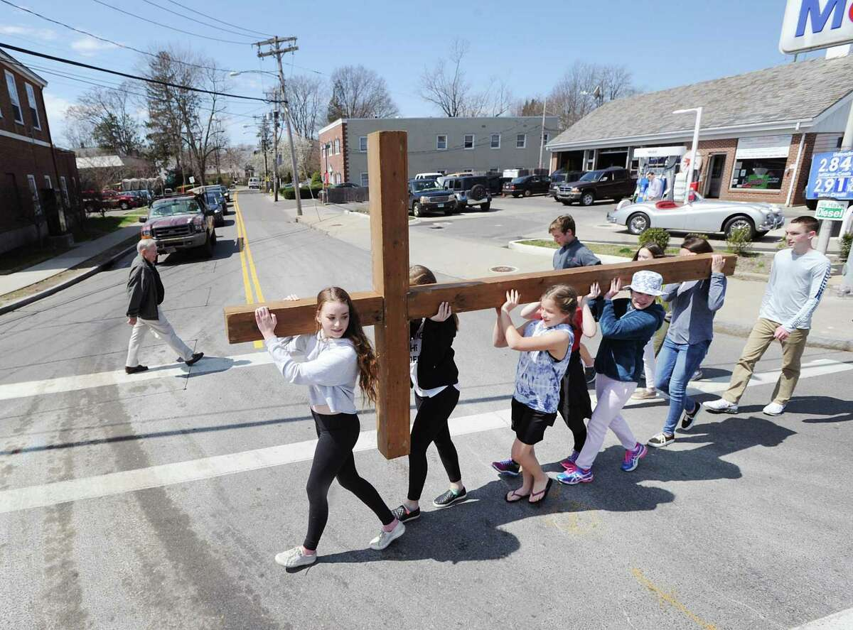 At right, Mariel Laffin, 14, center, leads the First Congregational Church of Greenwich Youth Group Cross Walk south on Sound Beach Avenue in Old Greenwich, Conn., Good Friday, April 14, 2017. Rev. Patrick Collins, First Congregational Church Associate Pastor of Children, Youth and Families, who was supervising the cross walk, said the group of about 10 kids carried the cross from Binney Park to Greenwich Point and that the cross will be used for the Easter Sunday sunrise service that takes places at 6 a.m. on the beach at Greenwich Point.