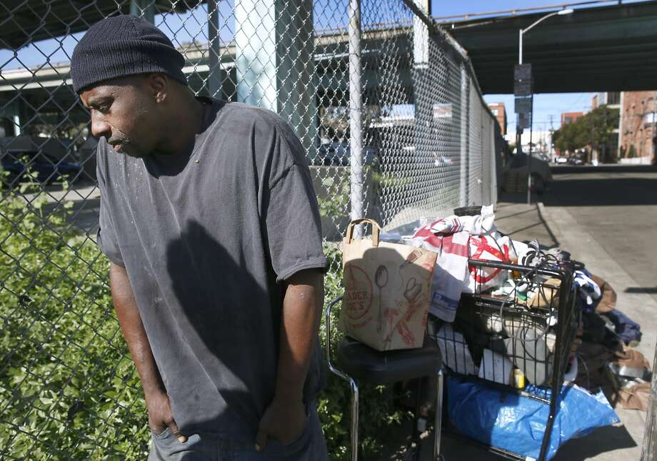 Above: Terrance Banks stands with his belongings at a homeless encampment at Vermont and 15th streets after having to move from a camp a block away after a sweep by city workers. Below: Darrell, who also relocated, rests at the camp. Photo: Paul Chinn, The Chronicle
