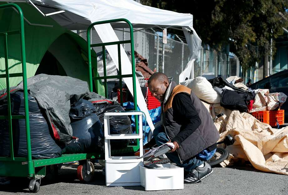 Ricky Walker reorganizes his belongings at a homeless encampment on Vermont Street in San Francisco in April. Photo: Paul Chinn, The Chronicle