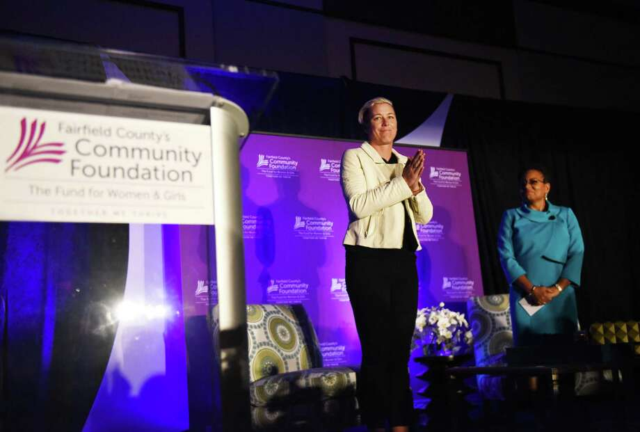 Retired U.S. soccer star Abby Wambach, center, is introduced by Fairfield County's Community Foundation Fund for Women and Girls Vice President Suzanne Peters to deliver the keynote speech at Fairfield County's Community Foundation's Fund for Women and Girls Annual Luncheon at the Hyatt Regency ballroom in Old Greenwich, Conn. Thursday, April 7, 2016. Wambach answered questions to the luncheon's theme - the strength, resiliency and power of women and girls. She also addressed her recent driving under the influence arrest, which occurred Sunday, April 3 in Portland, Oregon. Photo: Tyler Sizemore / Hearst Connecticut Media / Greenwich Time