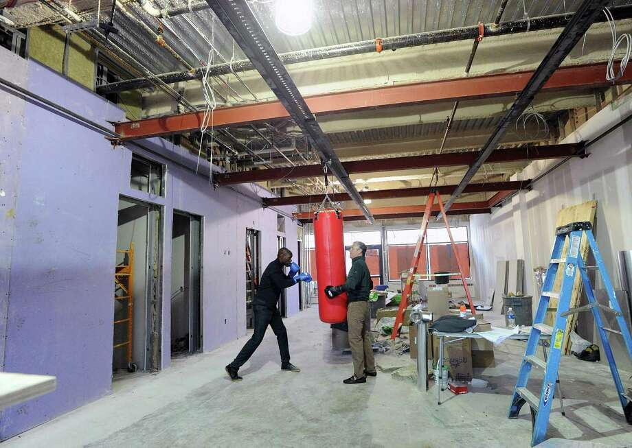 At left, Jonathan Edmond a co-owner of Belly and Body, a new independent boxing gym, works out on a punching bag as co-owner Jim Perry holds the bag in their gym that is under construction in Greenwich, Conn., Thursday, April 13, 2017. Edmond and Perry said their gym will be opening by the end of May. Photo: Bob Luckey Jr. / Hearst Connecticut Media / Greenwich Time