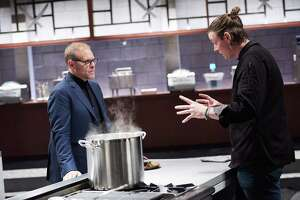 Host Alton Brown judges San Antonio chef Jason Dady's dish, Porcini Crusted Elk Loin with Red Currant Bordelaise, during the Chairman Challenge, as seen on Iron Chef Gauntlet, Season 1.