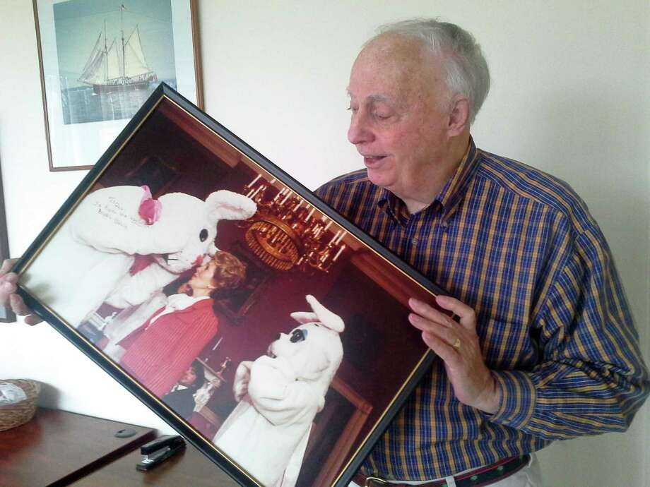 Greenwich resident E. Pendleton James holds a photograph of himself as the White House Easter Bunny speaking to First Lady Nancy Reagan. Photo: Ken Borsuk /