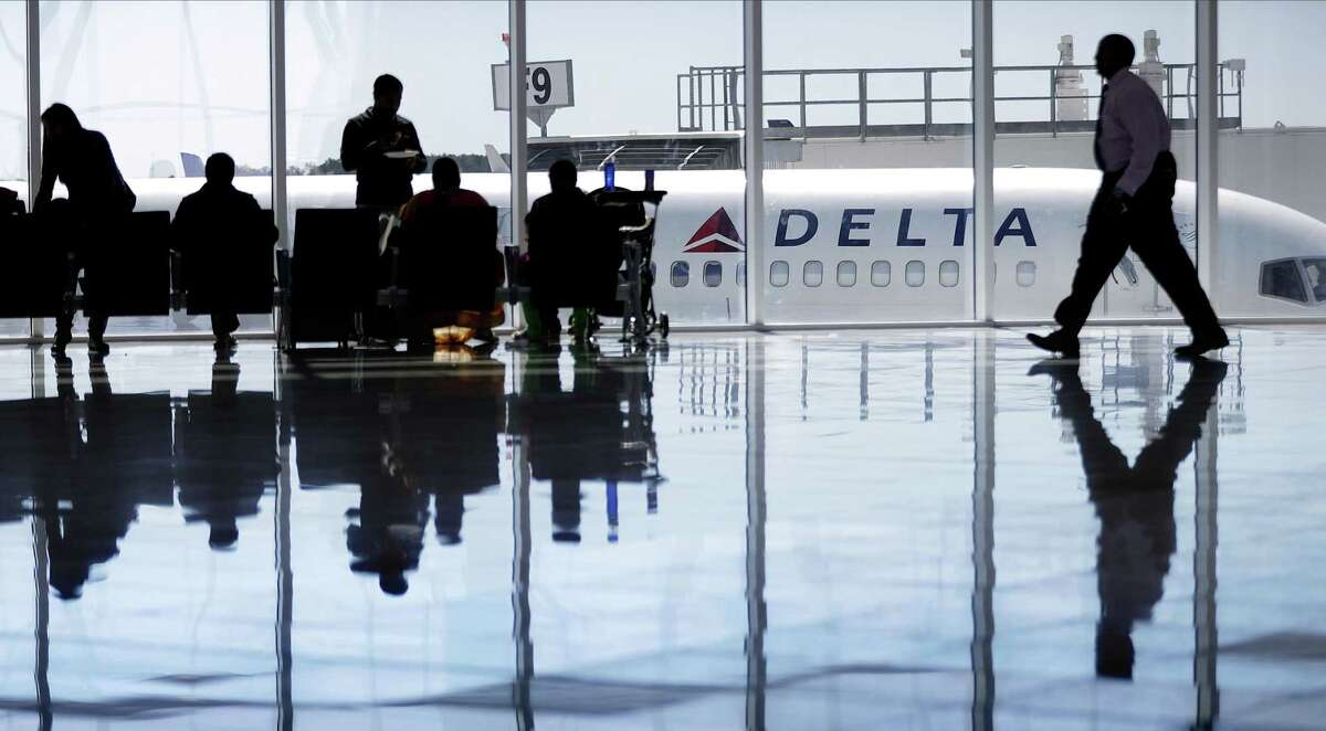 A Delta Air Lines jet sits at a gate at Hartsfield-Jackson Atlanta International Airport, in Atlanta. The airline says it is the first U.S. airline to use facial recognition technology to speed the process of checking baggage.