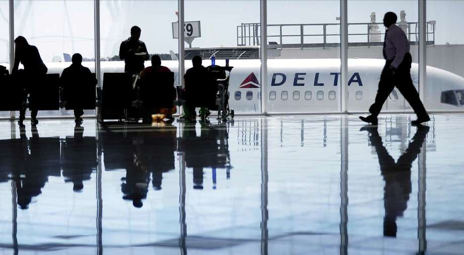 A Delta Air Lines jet sits at a gate at Hartsfield-Jackson Atlanta International Airport, in Atlanta. The airline says it is the first U.S. airline to use facial recognition technology to speed the process of checking baggage. Photo: Associated Press File Photo / Copyright 2016 The Associated Press. All rights reserved.