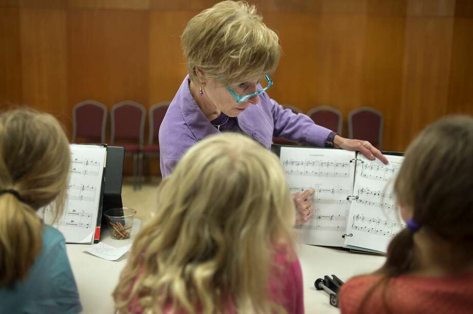 "Prime Chimers director Connie Nicholson, center, points out different notes to from left: 7-year-old Alexis Wilson,  8-year-old Alexa Warren and 9-year-old Katelyn Cassiday during a practice at United Methodist Church Wednesday afternoon. The Prime Chimers are practicing for the 40th Handbell Concert at the church April 23 at 7 p.m. The concert will feature songs from four handbell groups and is free to the public. The Prime Chimers will play ""Siyahamba"" and ""It's a small world"" at the concert. Photo: Brittney Lohmiller/Midland Daily News"