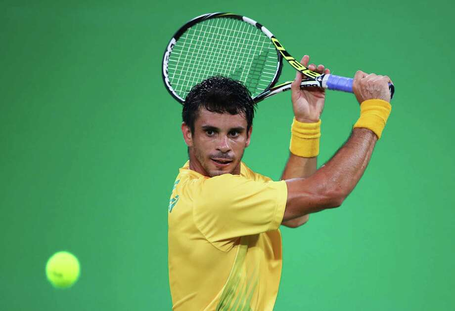 RIO DE JANEIRO, BRAZIL - AUGUST 08: Rogerio Dutra Silva of Brazil plays a backhand during the Men's Singles second round match against Gael Monfils of France on Day 3 of the Rio 2016 Olympic Games at the Olympic Tennis Centre on August 8, 2016 in Rio de Janeiro, Brazil. Photo: Clive Brunskill/Getty Images, Staff / 2016 Getty Images
