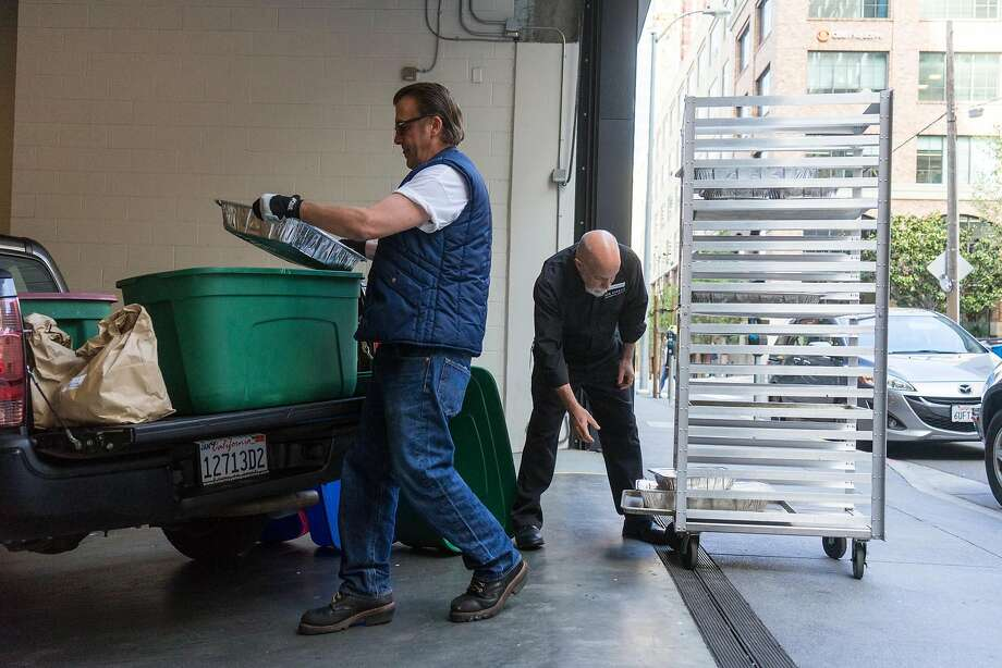 Denny Ray Miller (left) collects leftover food from networking company LinkedIn for Food Runners, which is in its 30th year. Photo: James Tensuan, Special To The Chronicle