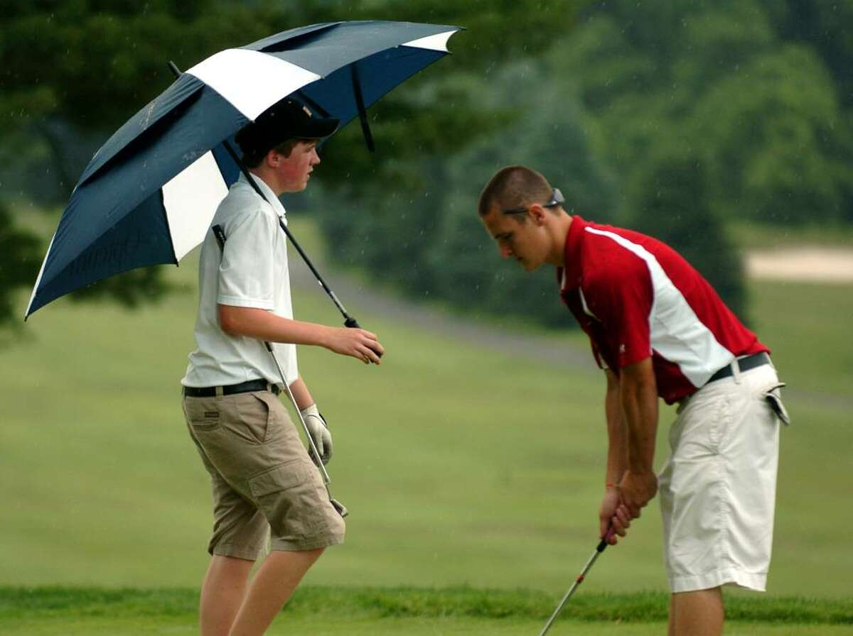 Trumbull's Chris Sarosky carries an umbrella as St. Joseph's Brian Kelly makes a practice stroke for his putt on the ninth hole, during boys FCIAC Championship golf action at Fairchild Wheeler Golf Course in Fairfield, Conn. on Thursday June 03, 2010. Just after this, a thunderstorm swept through the area causing the game to be suspended for about 45 minutes.