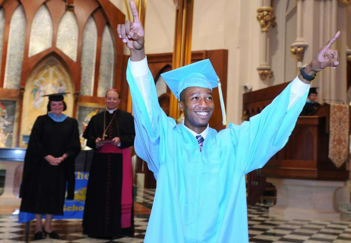 Daniel Carmichael throws his arms up to the crowd before accepting his diploma during the 2010 Kolbe Cathedral High School graduation ceremony Thursday June 3 at St. Augustine Cathedral in Bridgeport.