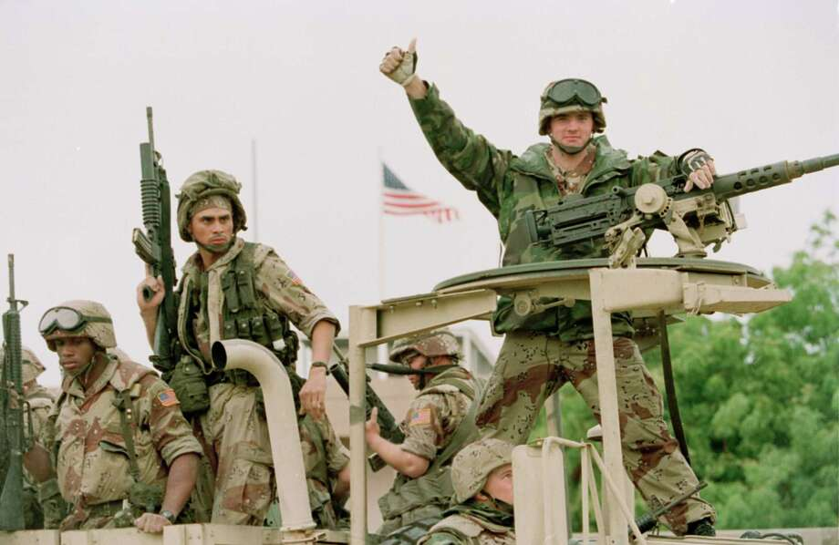 FILE - In a Dec. 10, 1992 file photo, a U.S. Marine gives the thumbs up as a truck load of troops arrive at the reopened U.S. Embassy in Mogadishu, Somalia.  According to the U.S. Africa Command on Friday April 14, 2017,  the U.S. military is sending dozens of regular troops to Somalia to train Somali soldiers in the largest such deployment to the Horn of Africa country in roughly two decades.   (AP Photo/Denis Pauqin, File) Photo: Denis Paquin, STF / AP1992
