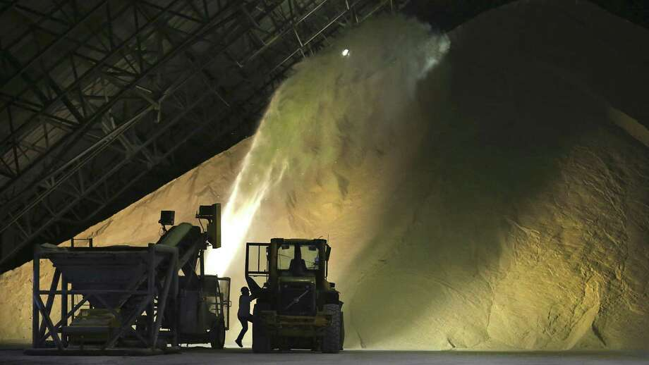An operator climbs into a front end loader as a spreader throws raw sugar on a roughly 30-foot-high pile in a storage warehouse at the W.R. Cowley Sugar House mill in Santa Rosa, Texas. The mill is owned by the Rio Grande Valley Sugar Growers, Inc., and has been operating since the 1970s. Photo: Bob Owen /San Antonio Express-News / ©2017 San Antonio Express-News