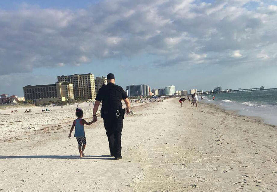 Clearwater, Fla. police officer Rich Edmonds holds the hand of 6-year-old Hannah, who had wandered away from her family on the beach and approached another family who called police for assistance.  Photo: Amy Amerell, HONS / Amy Amerell