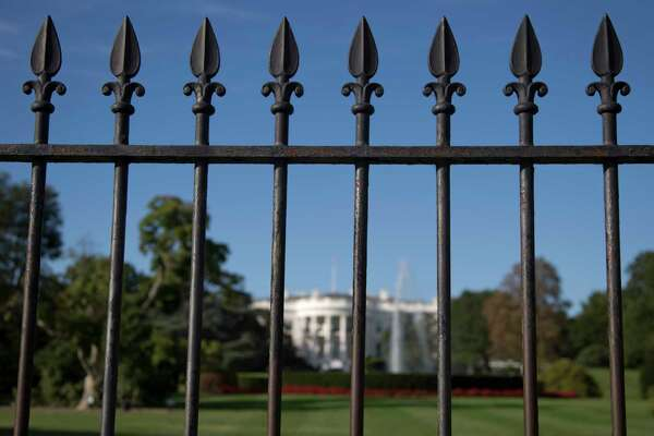 In this photo taken sept. 22, 2014, the iron perimeter fence lines the South Lawn of the White House in Washington. Two Secret Service officers who were on duty the night a man jumped the White House fence and spent more than 15 minutes roaming the grounds have been told the agency intends to fire them. (AP Photo/Carolyn Kaster) ORG XMIT: WX103