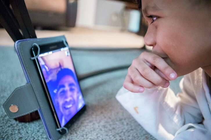Walter Escobar speaks to his father Jose Escobar using a tablet, Tuesday, April 11, 2017, in Pearland. Walter's father was deported to El Salvador about six weeks ago after Jose reported for a routine immigration appointment. Now Jose's two children and wife depend on electronics to keep him involved in their lives.