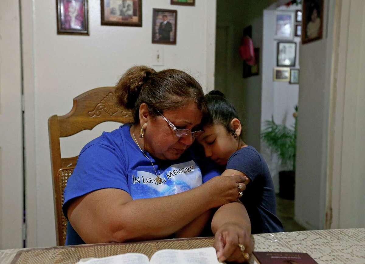 Janie Villarreal (left), is hugged by her granddaughter Amaryss Pena, 4, at Villarreal's home on March 16, 2017. Janie Villarreal's son Anthony Villarreal was killed in 2013, and police have not solved the case.