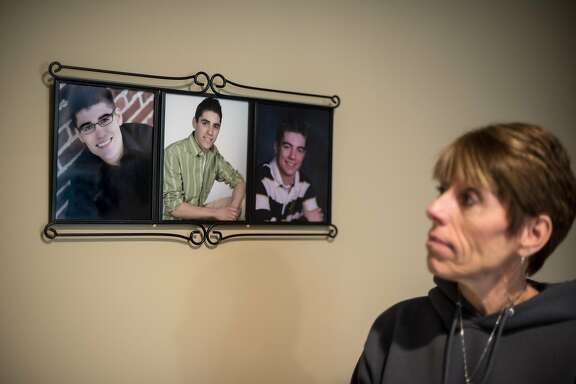 Peggy Riggs looks at photographs of her three sons in her home in Oakdale, Minnesota on Saturday, April 8, 2016. Peggy's youngest son David (left photo) died after being hit by a driver who was texting and driving in 2013. Since then, Peggy and her husband Craig have worked to educate people on the dangers of texting and driving and have pushed for stricter laws against it.