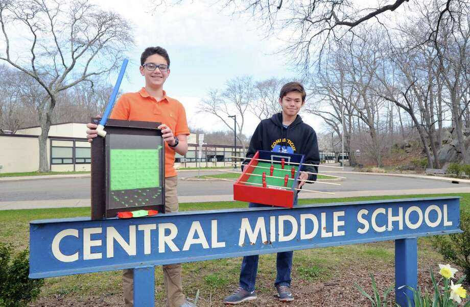 Central Middle School 7th grade students Ben Fertig, 13, left, displays the pinball game he made as classmate Justin Jacob, also 13, displays the foosball table he constructed at Central Middle School in Greenwich, Conn., Friday, April 14, 2017. Both teens, along with other students in Kate Bruzinski's science class, made toys, some fabricated with a 3-D printer, that are being donated to an orphanage in Haiti. Photo: Bob Luckey Jr. / Hearst Connecticut Media / Greenwich Time