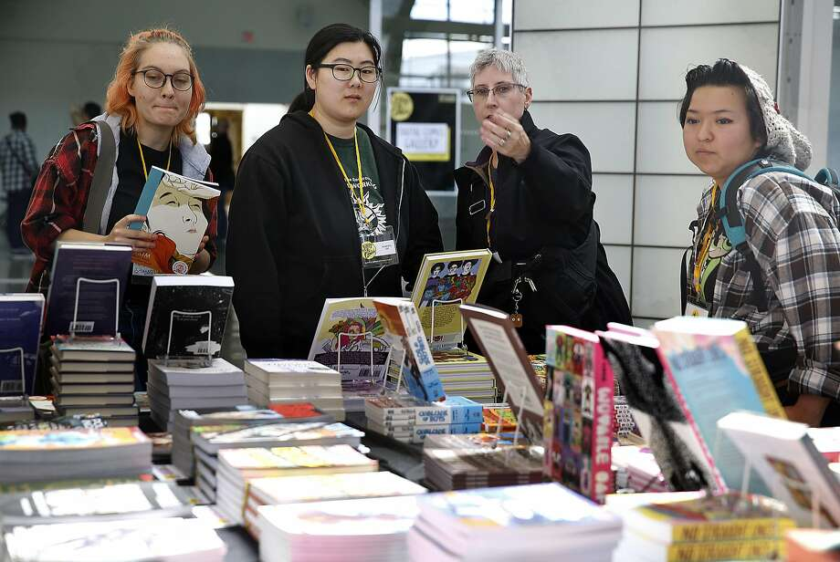 Writer and editor Erica Friedman (second from right) from New Jersey shows writer Mary Bridgens (left), Roberta Lee (second from left), and Melissa Pacheca (right) books edited by her at the Queers & Comics Conference bookstore at the California College of the Arts on Friday, April 14, 2017, in San Francisco, Calif. Photo: Liz Hafalia, The Chronicle