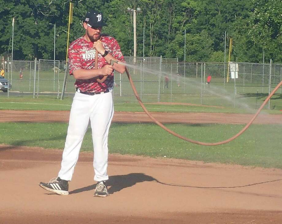 Danbury Westerners manager Josh Parrow hoses down the infield prior to the game against the Mystic Schooners at Rogers Park June 17, 2016. Photo: Richard Gregory / Richard Gregory