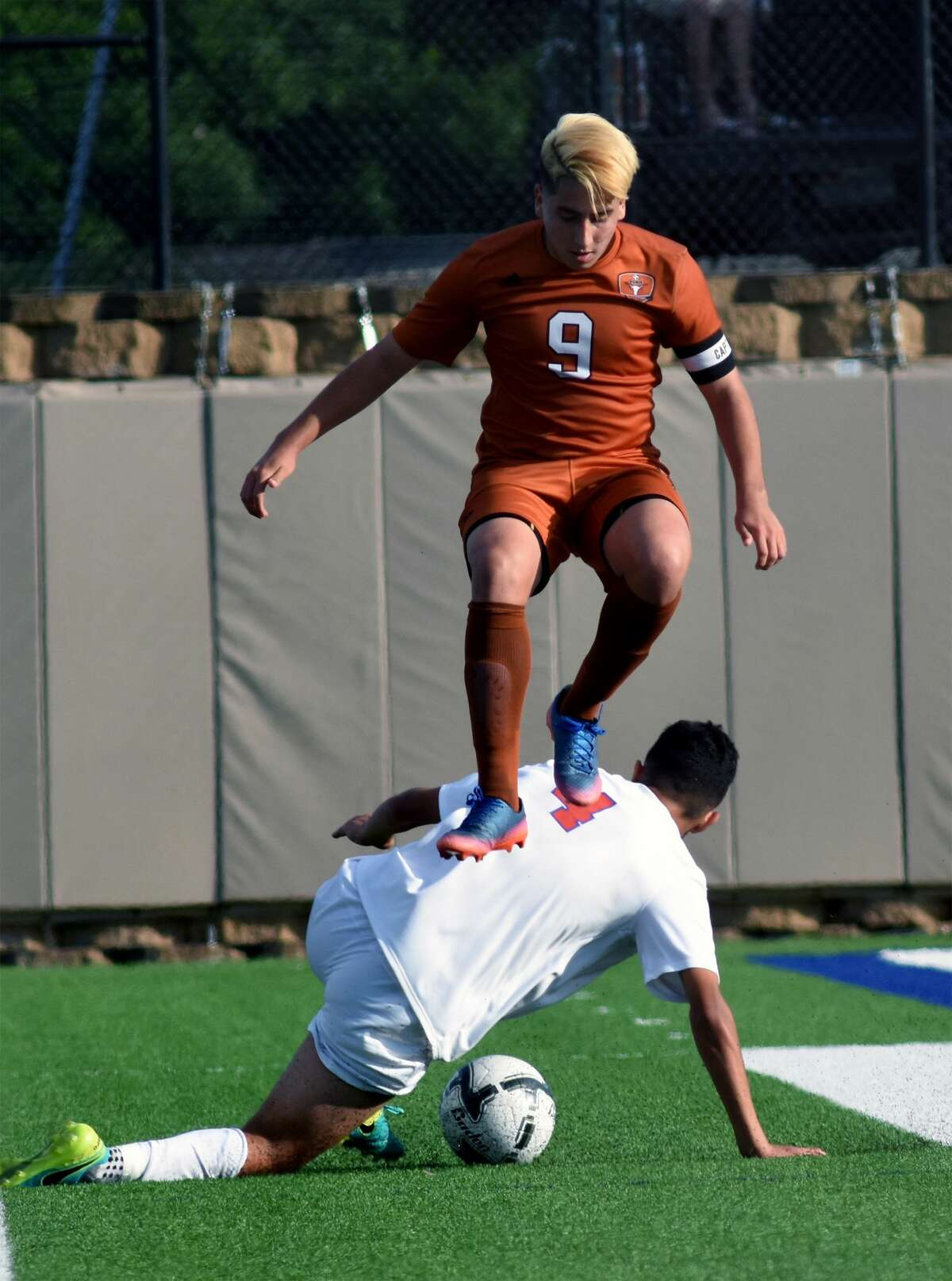 Dobie senior forward Sabino Lozano (9) jumps over Arlington Houston's Mario Trevizo while making a play in the first period of their Class 6A Boys semifinal matchup at the 2017 UIL Soccer State Championships at Birkelbach Field in Georgetown on April 14, 2017. (Photo by Jerry Baker/Freelance)