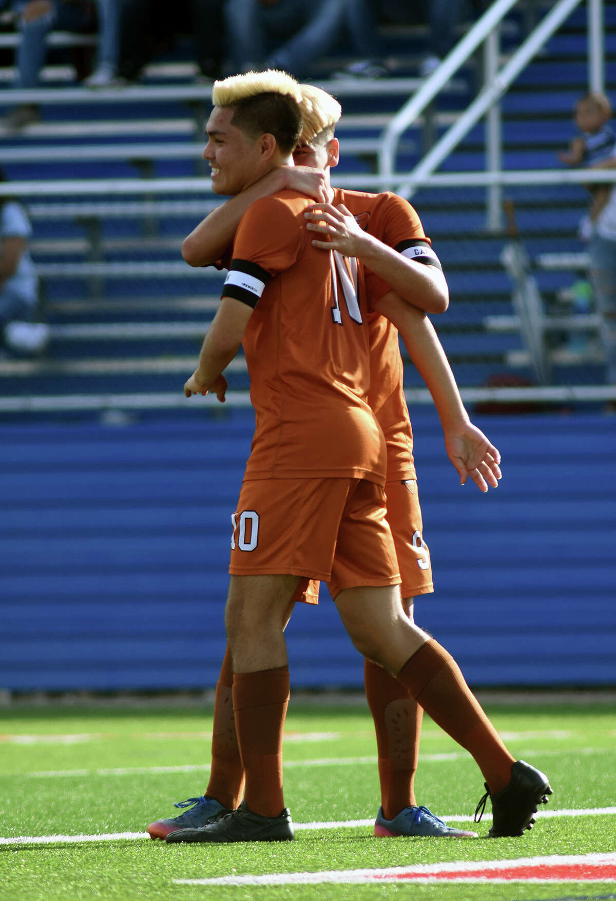 Dobie senior midfielder Edwin Saldivar, left, gets a hug from fellow team captain and senior forward Sabino Lozano after Saldivar converted on a penalty kick for a Longhorn goal against Arlington Houston early in the first period of their Class 6A Boys semifinal matchup at the 2017 UIL Soccer State Championships at Birkelbach Field in Georgetown on April 14, 2017. (Photo by Jerry Baker/Freelance)