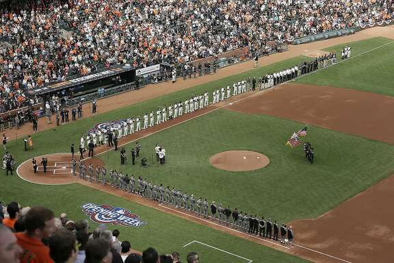 Members from the cast of the musical Hamilton sing the national anthem on opening day as the San Francisco Giants, top, and Arizona Diamondbacks, bottom, line the bases before the start of a baseball game, Monday, April 10, 2017, in San Francisco. (AP Photo/Eric Risberg)