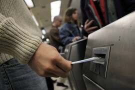 A BART passenger runs his fare ticket through the exit gate at the Rockridge BART station on Monday, October 28, 2013. BART riders who run out of fare on their tickets or Clipper cards have to add fare to leave their arrival station. But many complain that the machines only take cash and not credit cards like the ticket machines out side the gates, forcing passengers to ask for help from station agents or fellow passengers.